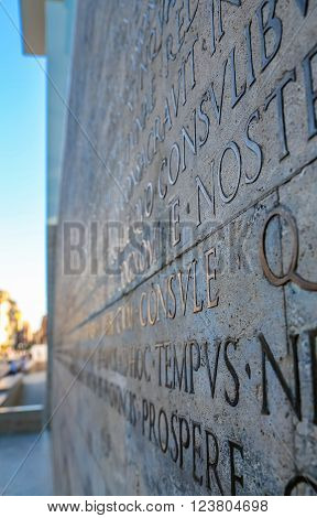 Latin inscription on the outside wall of the peace altar in Rome. Ara Pacis wall in Rome, Italy