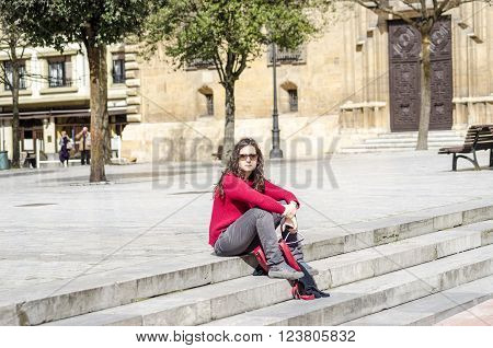 Young woman sitting and relaxing in a sunny day a square of Oviedo Asturias Spain.