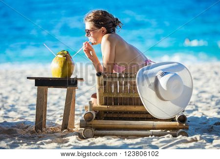 Young woman drinking coconut juice while relaxing on the beach