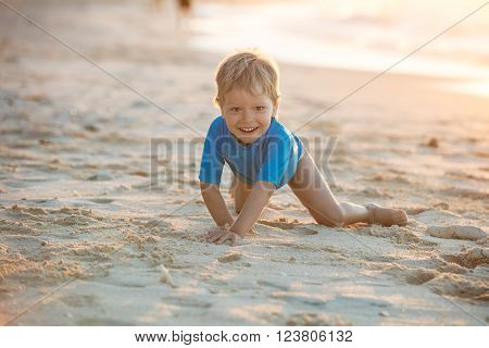 Happy little boy playing on beach. Sunset light.