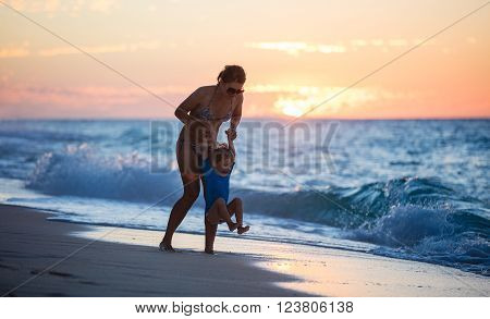 Young mother and son having fun on the beach at sunset