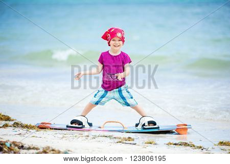 Young boy standing on board for kitesurfing and smiling