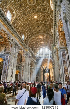 Vatican, Italy - June 26, 2014: People at the interior of the Saint Peter Cathedral in Vatican. Saint Peter's Basilica has the largest interior of any Christian church in the world.
