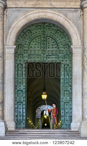 Vatican Italy - June 26 2014: Vatican guard stands in front of Vatican Museum in Vatican Rome Italy. The Swiss Guards are responsible for the security of Vatican.
