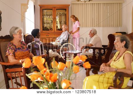 Old people in geriatric hospice: young attractive hispanic woman working as nurse helps a senior man on wheelchair. He joins a group of friends playing chess and having fun