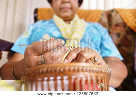Old people in geriatric hospice: Senior woman sitting on sofa in hospital knitting with ball of wool. The aged lady is pensive and focused on her hobby.
