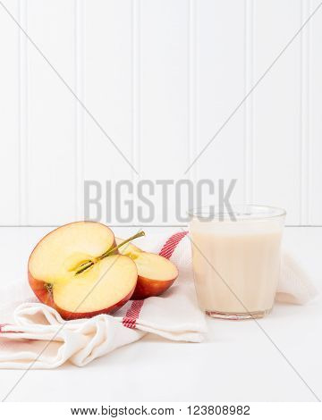 Snack of fresh red apple and a glass of cold milk.