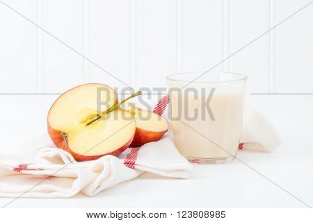 Snack of sliced fresh red apple and a glass of cold milk.