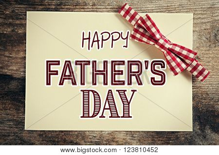 Happy Father's Day. Red cell bow tie on wooden background