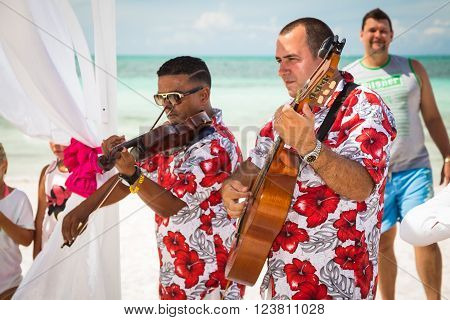 Cayo Coco island, Playo Coco, Cuba - September 10, 2015: Closeup view of two musicians playing at a wedding ceremony on tropical beach.