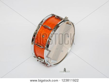 closeup view of wooden mahogany color snare drum isolated on light grey background