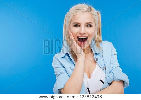 Cheerful charming woman standing over blue backgorund