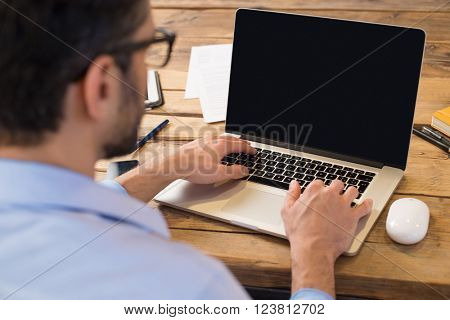 Back view of businessman sitting in front of laptop screen. Man typing on a modern laptop in an office.