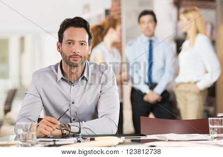 Portrait of a young handsome business man holding glasses looking at camera in working environment. Satisfied businessman with his colleagues in background looking at camera in a meeting in office.
