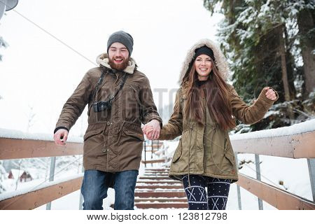 Happy young couple holding hands and running down the stairs in winter