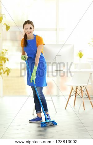 Woman cleaning floor with mop indoors