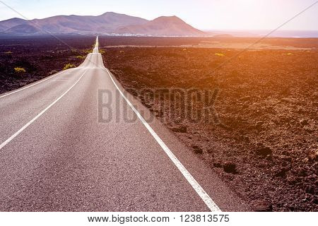 Highway on the deserted landscape on the sunset on Lanzarote island in Spain