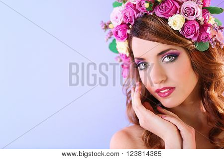 Beautiful young woman wearing floral headband on a purple background