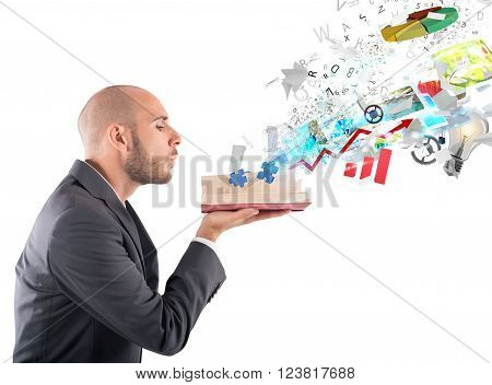 Businessman blowing over a magic business book