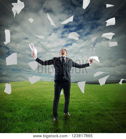 Businessman in a meadow rejoices throwing sheets