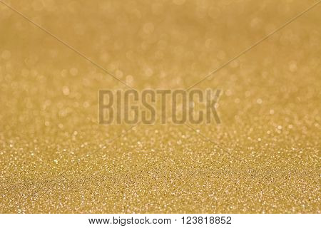 Closeup abstract defocused background glittery texture photo of glitter in golden yellow shade. Selective focus with Bokeh light
