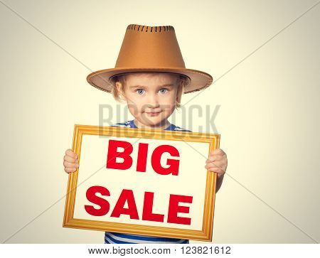 Little Funny girl in striped shirt with blackboard. Text  big sale.  Isolated on gray background.
