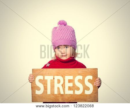 Little girl holding Board with inscription Stress. Isolated on gray background