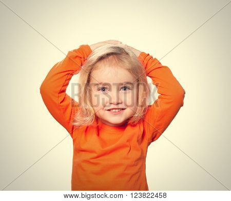 Little Funny girl in orange blouse holding his head. Isolated on gray  background