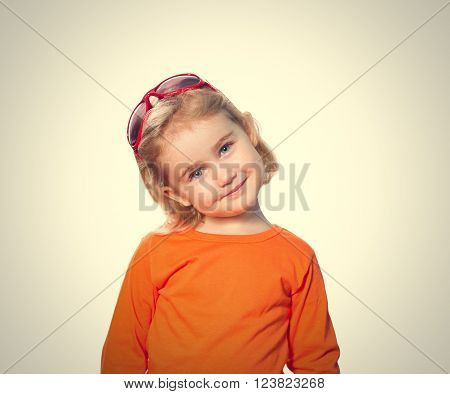 Little girl in red sunglasses on head . Isolated on gray  background