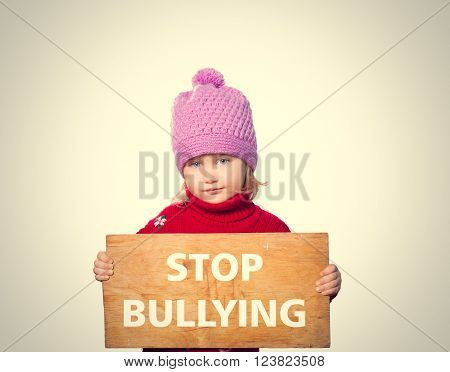 Little girl holding Board with text STOP BULLYING. Isolated on gray background.