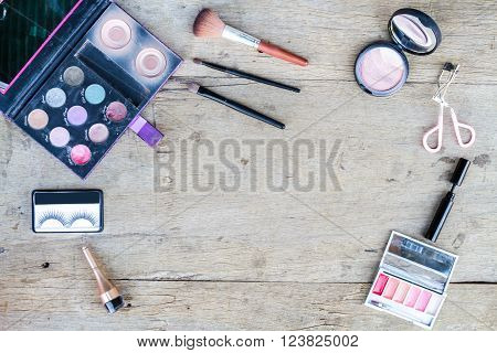 Cosmetics with eye shadow, eye liner, powder, eyelash curler on wood table. Top view.