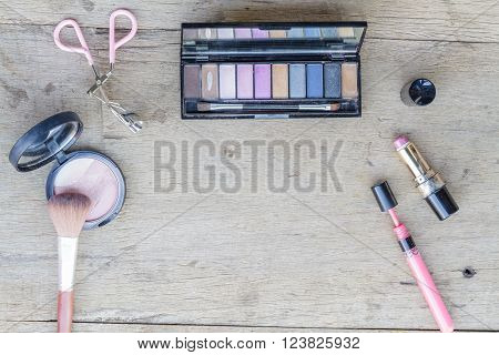 Cosmetics with eye shadow, eye liner, powder, lipstick,  and eyelash curler on wood table. Top view.