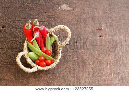 Chili, sweet peas and cherry tomato inside small rattan basket on old wooden table. Selected focus.