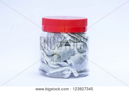 Tea bags in plastic jar with red lid on isolated white background