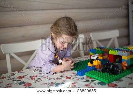 sad child girl play educational toys in home little Caucasian girl sisters playing constructor on table casual lifestyle photo series in real life interior