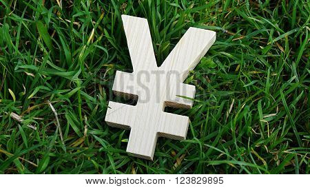 Yuan sign of wood isolated on grass