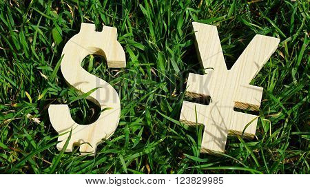 Exchange currency unit on a grass background. Wooden sign.