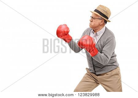 Angry senior with red boxing gloves prepared for a fight isolated on white background