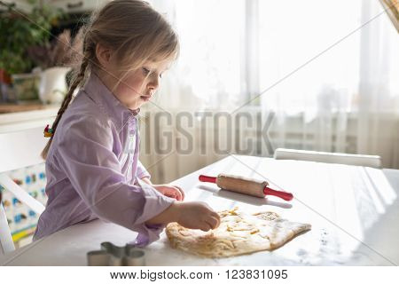 little Caucasian girl with pigtails makes the cookies from the dough cutting out dough for cookies cute childcasual lifestyle photo series in real life interior