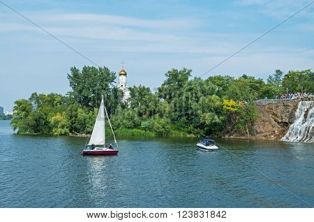 Dnepropetrovsk Ukraine - September 14 2013: Pleasure yacht floating on water in the river on a background of green Island