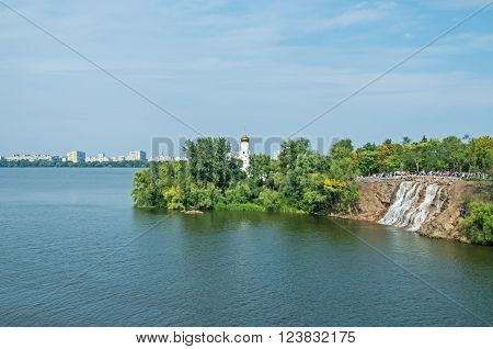 View of the green river island with church and waterfall on a clear sunny day