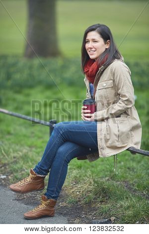 Young female holding her coffee cup while sitting on the park railing