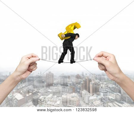 Man carrying golden dollar sign balancing on tightrope with woman hands holding two sides on cityscape background.