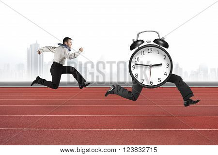 Man running after alarm clock of running legs on red running track with city skyline background.