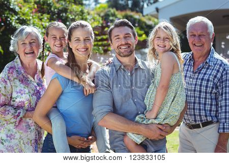 Portrait of happy family standing in back yard during sunny day