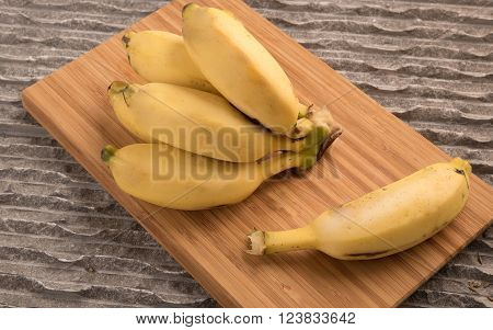 Bananas bunch and a single babana on a wooden pannel