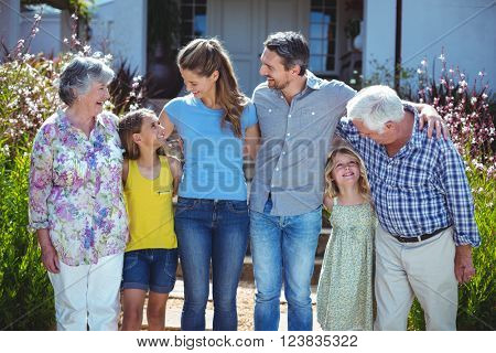 Cheerful multi-generation family looking at each other against house