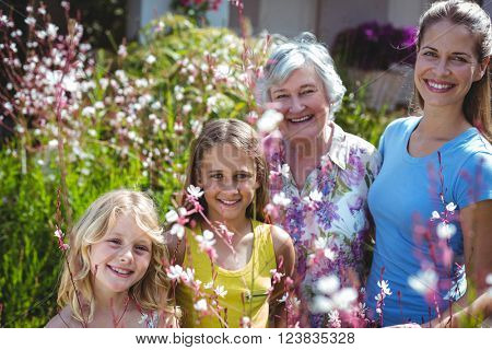 Happy senior woman with daughter and girls in back yard during sunny day