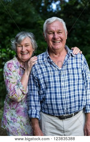 Portrait of cheerful senior couple standing in back yard