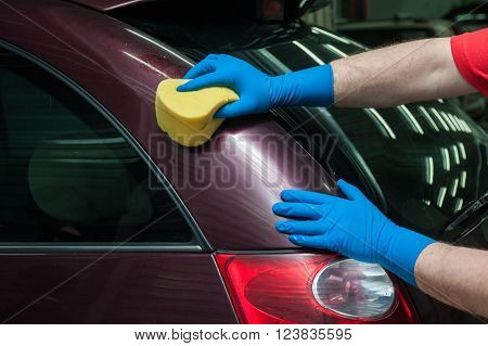 hand with sponge over the car for washing